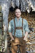 young man in bavarian lederhosen in front of firewood - stock photo
