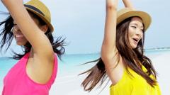 Portrait of happy multi ethnic girlfriends on beach - stock footage