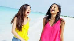 Laughing young African American Asian Chinese girls on beach - stock footage