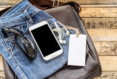 Brown leather bag,blue jean,smart phone and earphone on wooden table Stock Photos