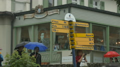 Tourists passing by a street signboard in Schwangau, Neuschwanstein Castle Stock Footage