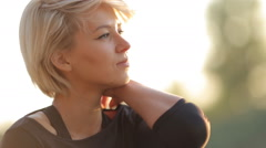 The beautiful blonde has a rest after a workout at sunset in the rays of light Stock Footage