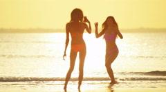 Barefoot multi ethnic female in bikini taking selfie on beach Stock Footage