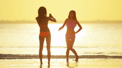Young African American Asian Chinese girls in swimwear on beach - stock footage