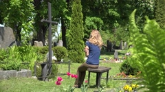 Stressed girl shrink near father husband tomb in graveyard. 4K Stock Footage