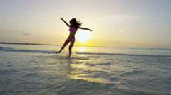 Barefoot ethnic girl carefree dancing on tropical ocean beach Stock Footage