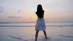 Beautiful Asian Chinese female dancing on tropical beach - stock footage