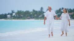 Male female senior Caucasian couple in white clothes on a beach - stock footage