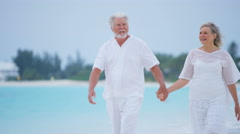 Retired senior Caucasian couple walking barefoot on a tropical beach - stock footage