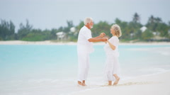 Retired Caucasian senior couple walking barefoot on a beach - stock footage