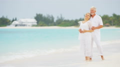 Retired senior Caucasian couple standing barefoot on a tropical beach - stock footage