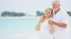 Caucasian senior retired couple sharing a kiss on a tropical beach - stock footage