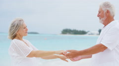 Retired senior Caucasian couple dancing together on a tropical beach - stock footage
