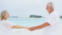Retired senior Caucasian couple dancing on a tropical beach - stock footage