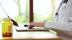 Female doctor's hands typing on laptop in clinic Stock Footage