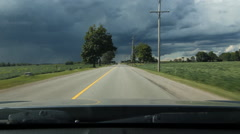 Driving towards storm in rural area. Fields and hydro poles. Ontario, Canada. Stock Footage