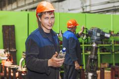The young man working at the old factory on installation of equipment - stock photo
