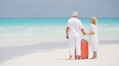 Retired senior vacation couple on a tropical beach with travel luggage - stock footage
