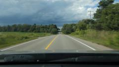 Driving on sunny road with storm ahead. Going over crest of hill. - stock footage