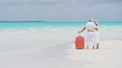 Male female Caucasian seniors on a tropical beach with a suitcase - stock footage