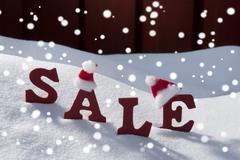 Christmas Sale On Snow Santa Hat And Snowflakes Stock Photos