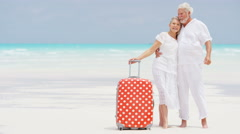 Caucasian senior travellers outdoors on a beach with a suitcase Stock Footage