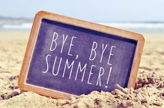 Text bye, bye summer in a chalkboard on the beach Stock Photos