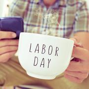 Young man with a mug with the text labor day Stock Photos