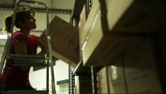 A beautiful girl picked up a box with a scale of one shelf. Backlight Stock Footage