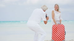 Retired couple having fun on a tropical beach with a suitcase and camera - stock footage