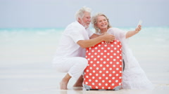Caucasian seniors on a tropical beach taking a selfie with their suitcase - stock footage