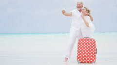 Retired couple having fun on a tropical beach taking a selfie with a suitcase Stock Footage