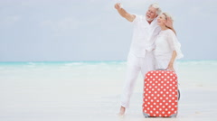 Caucasian seniors on a tropical beach taking a selfie with their suitcase Stock Footage