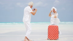 Barefoot mature Caucasian couple outdoors on a beach with a suitcase and camera - stock footage