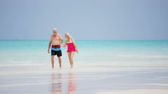 Senior Caucasian couple in swimwear together on an island beach - stock footage