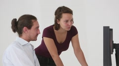 Young colleagues working together in office, smiling Stock Footage