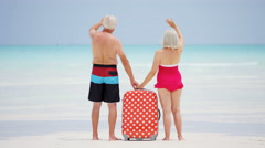 Barefoot mature Caucasian couple in swimwear on a beach with a suitcase - stock footage