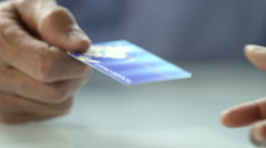 Credit card handed to clerk, close up on card Stock Footage