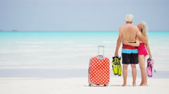 Caucasian seniors on a beach with a suitcase and snorkels - stock footage