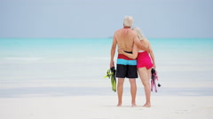 Retired couple in swimwear on a tropical beach with snorkel equipment - stock footage