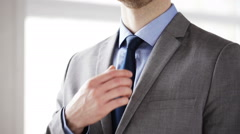 Stock Video Footage of close up of man in suit adjusting necktie