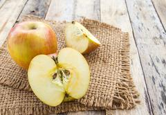 Fresh apples in burlap sack on wooden table background - stock photo