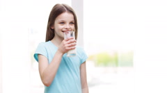 Happy smiling little girl drinking milk at home Stock Footage
