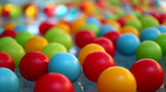 Many colorful plastic toy balls floating in a children swimming pool water Stock Footage