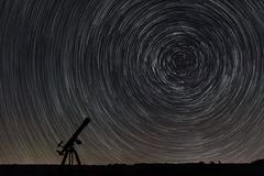 Beautiful night sky, Star trails over filed and astronomical telescope Stock Photos
