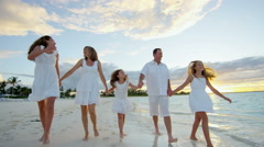 Caucasian family walking barefoot on beach together at sunset - stock footage