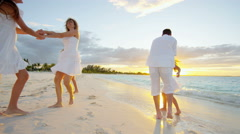 Caucasian family walking barefoot on beach together at sunset Stock Footage
