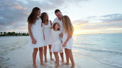 Caucasian family barefoot on a beach together at sunset - stock footage