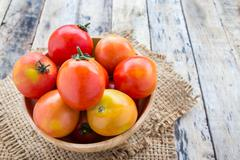 Fresh tomatoes on wooden table - stock photo