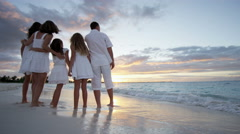 Happy Caucasian family enjoying a beach vacation at sunset - stock footage